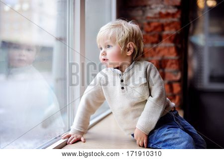 Toddler boy sitting on the window sill and looking at the panoramic window