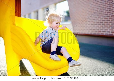 Funny toddler boy having fun on slide on playground. Active game for little child