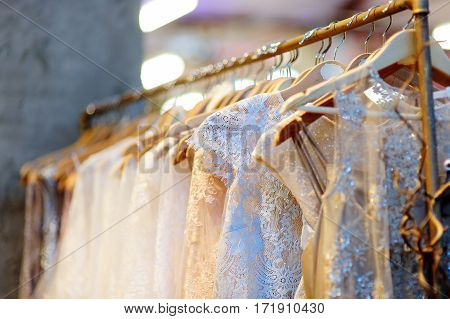 A few beautiful wedding dresses on a hanger. Clothes for bride or bridesmaids