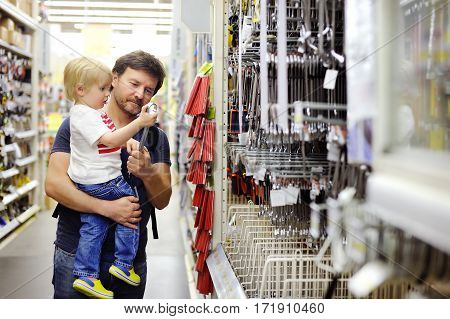 Father And His Son Choosing The Right Tool In A Hardware Store
