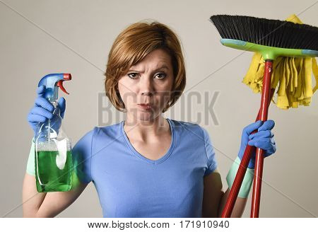 beautiful stressed service woman or housewife in washing rubber gloves carrying cleaning spray bottle broom and mop frustrated and overworked tired and lazy in housework stress