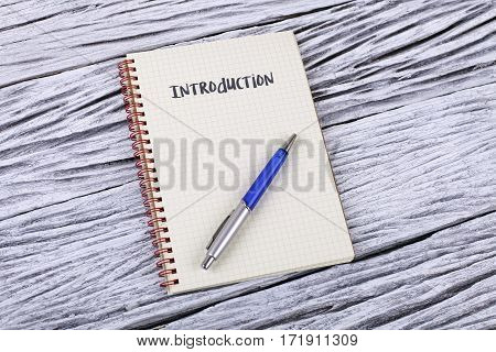 Introduction example on a notepad wooden background
