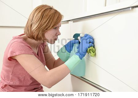 young attractive red hair woman or housewife leaning on kitchen with rubber washing gloves cloth detergent cleaning bored and tired in stress of domestic housework concept
