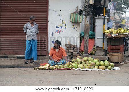 KOLKATA, INDIA - FEBRUARY 10: Unknown Indian sells coconuts on a city street in Kolkata on February 10, 2016.