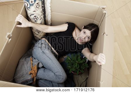 a young woman and her belongings, stuffed into a crate. maybe she was thrown out of her apartment