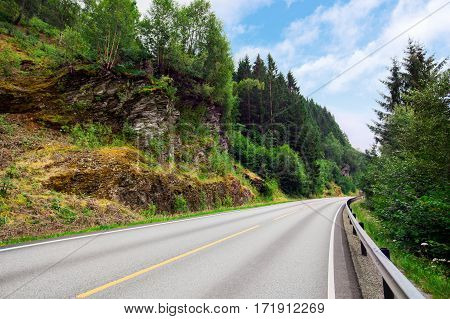 road mountain through asphalt highway landscape forest sky travel nature mountains drive green winding beautiful view trip rural scenic summer journey grass line way woods day outdoors transportation route