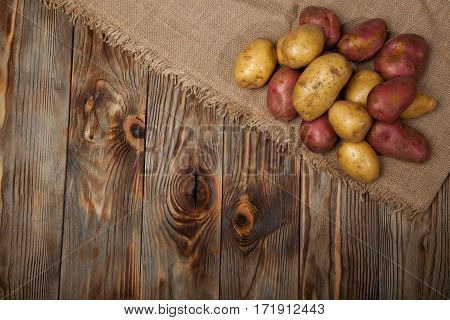 Raw potato food . Potatoes in an old box on a wooden table . Free space for text. Top view