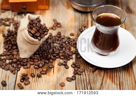 Freshly made coffee in a white cup surrounded by coffee beans on a wooden table. Fresh roasted coffee.