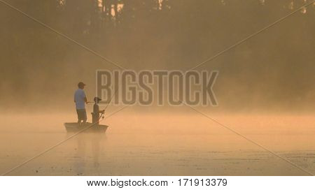 Early Morning Sunrise Father and Son Fishing on Serene Lake with Fog Lifting off the Water