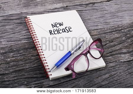 Note with New Release on the wooden background poster
