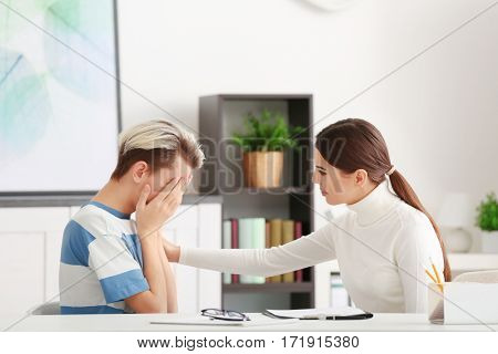 Young female psychologist working with teenager boy in office