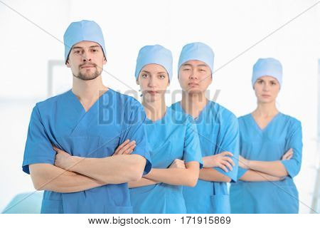 Handsome young doctor with colleagues in clinic