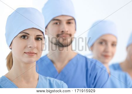 Beautiful young doctor with colleagues in clinic