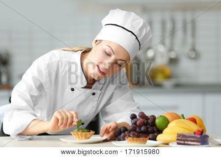 Female chef decorating fruit tartlet in kitchen