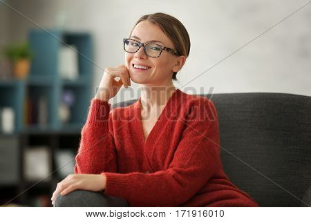 Young woman sitting on armchair in living room