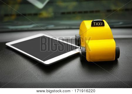 Yellow toy taxi with tablet on car dashboard