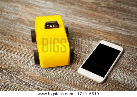 Yellow toy taxi with phone on wooden background
