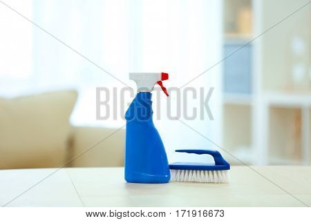 Brush and bottle with detergent on wooden table indoors