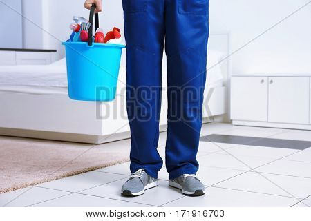 Legs of young man with cleaning supplies at home