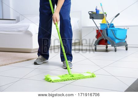 Legs of young man moping floor at home