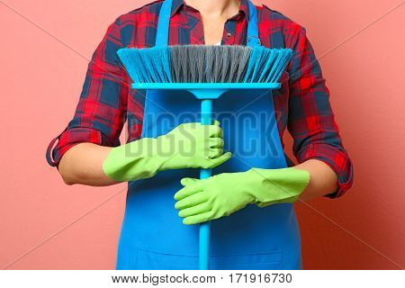 Young cleaner with brush on pink background