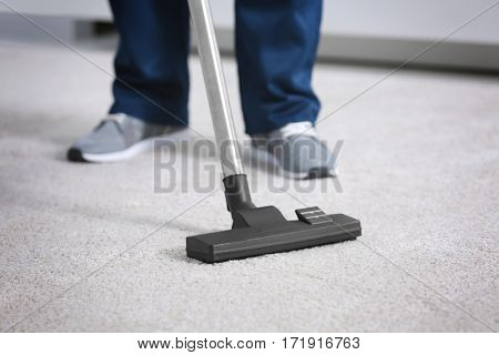 Legs of man hoovering carpet with vacuum cleaner