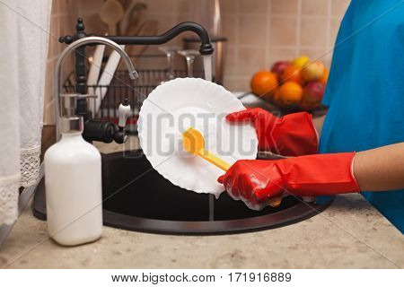 Child hands washing dishes at the sink - scrubbing a plate with a brush, shallow depth