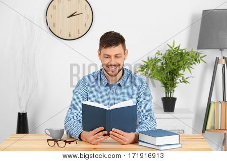 Handsome young man reading book at home