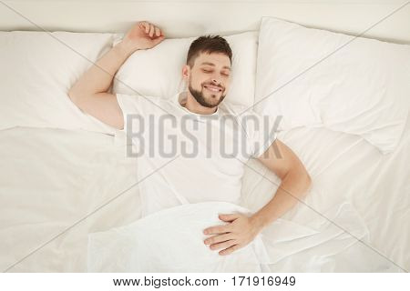 Young attractive man sleeping in bed at home