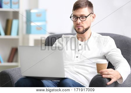 Handsome young programmer working with laptop at home