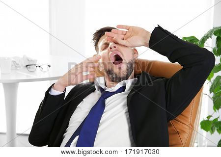 Tired business man yawning and stretching at workplace in office