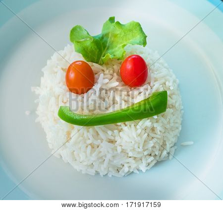 A portion of white rice on a plate shaped as a face using a slice of green bell pepper two cherry tomatoes and a salad leaf.