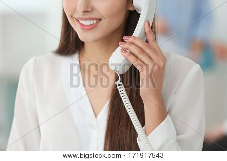 Beautiful young woman talking by telephone while working in office, closeup