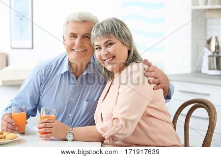 Beautiful mature couple with orange juice sitting at kitchen table