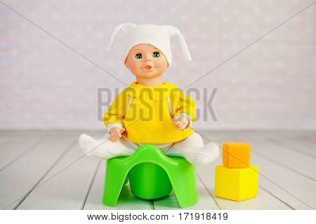 Doll, baby toy sit on green toilet potty
