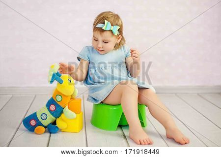 lovely baby boy with toys and waffle sitting on potty