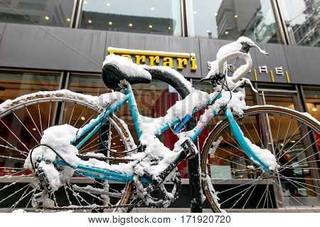 New York February 9 2017: A snow covered bycicle stands chained to a rack in front of the Ferrari store on Park Avenue.