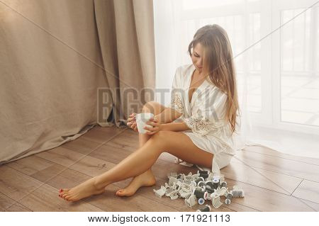 Sweet Young housewife sitting on the floor near the window. Girl in bathrobe removed the curlers. Good morning. She is drinking morning coffee
