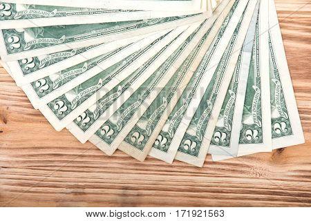 Fan of two dollar bills on vintage wooden background