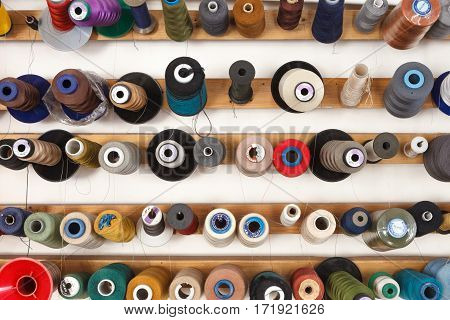 Spools of colorful thread on the wall. Hobby background
