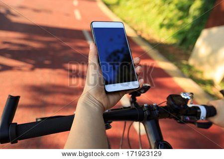 closeup of hands use gps navigator on cellphone while biking