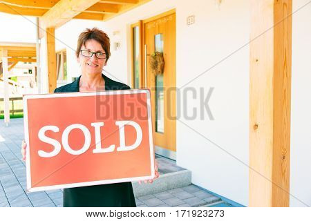 realtor selling a house, holding poster in front of the building