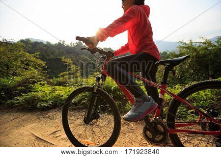 young woman cyclist riding mountain bike on forest trail