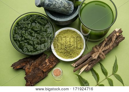 Medicinal Ayurvedic Azadirachta indica or Neem leaves in mortar and pestle with neem paste, juice and twigs, powder and oil, selective focus