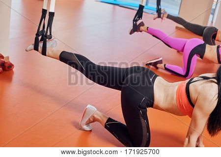 Beautiful young womens legs. women doing exercises with TRX