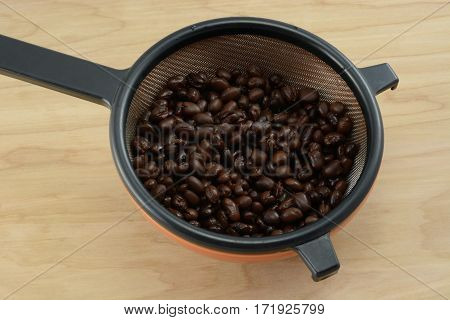 Rinsed canned black beans draining in strainer in bowl