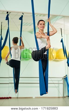 Young woman doing aerial yoga exercise or antigravity yoga indoor. Fitness, stretch, balance, exercise and healthy lifestyle people. Woman using hammock.