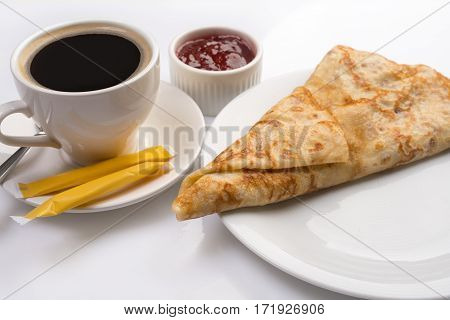 Pancake rolled in triangle form served with jam and black coffee close up shot