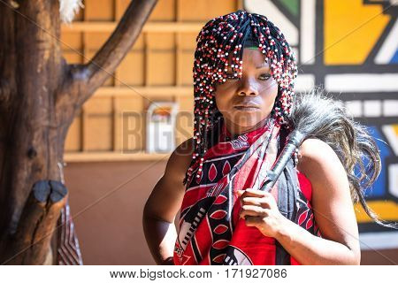 Lesedi Cultural Village, SOUTH AFRICA - 4 November 2016: Young Zulu woman in colouful traditional  costume with beaded hair