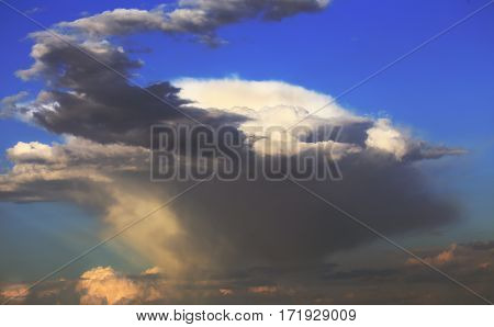 Spinning mushroom cloud in the blue sky at the stage of formation of a hurricane